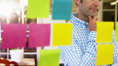 Male business executive looking at sticky notes Live Action