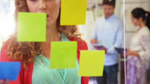 Female executive looking at sticky notes while using laptop Live Action