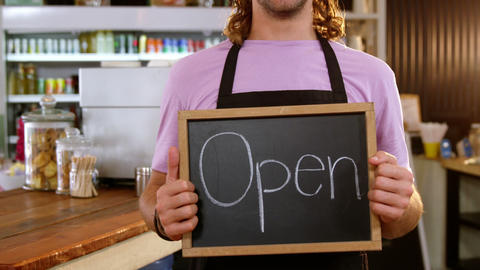 Waiter holding chalkboard with open sign Stock Video Footage