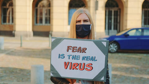 Woman in mask protesting that fear is the real virus on protest march Live Action