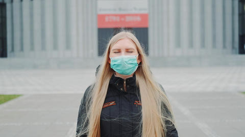 Medium shot of blonde woman in a medical mask walking down the street Live Action