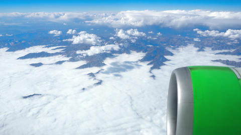 Beautiful view through airplane window, airplane flying above the clouds and mou Live Action