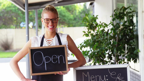Portrait of waitress holding a chalkboard with open sign Live Action