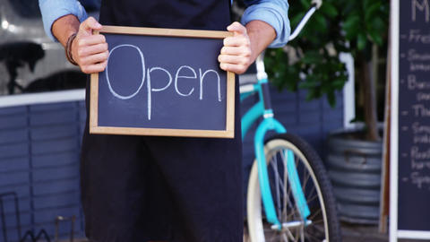 Waiter showing chalkboard with open sign Footage