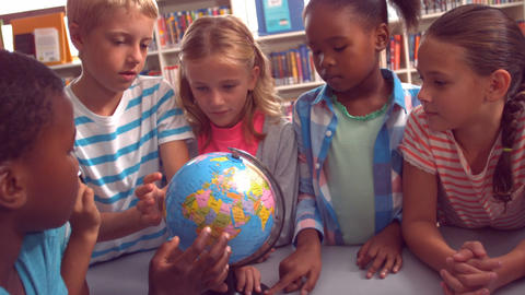 Kids studying over globe in library Footage