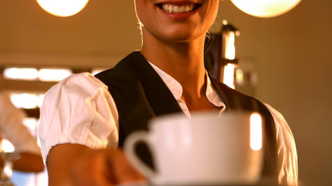 Mid-section of female waitress serving a cup of coffee Footage