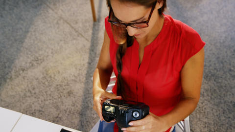 Female graphic designer using graphics tablet and looking at digital camera Live-Action