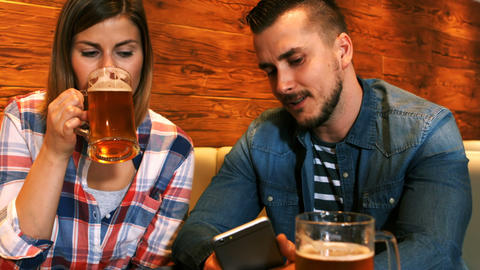 Couple using mobile phone while having a glass of beer Footage