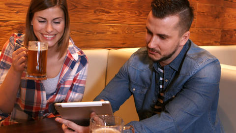 Couple using digital tablet while having a glass of beer Footage