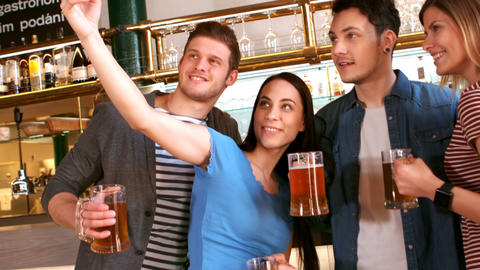Friends taking selfie from mobile phone while having a glass of beer Live Action