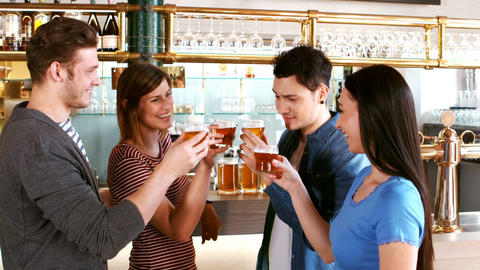 Happy friends toasting a glass of whisky at bar counter Footage