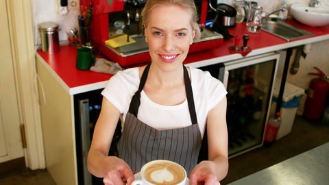 Portrait of smiling waitress offering cup of coffee at counter Footage