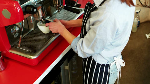 Waitress making cup of coffee at counter Footage