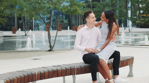 Cheerful multiracial couple having date outdoors near the fountains Live Action