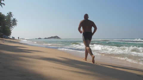man fights with unhealthy lifestyle running along shore Live Action