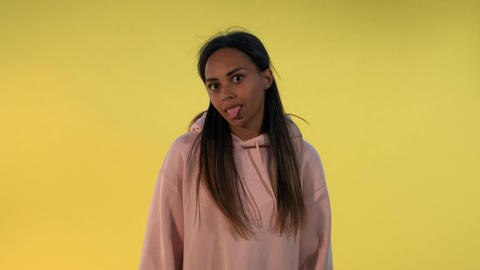 Multiethnic girl making funny faces on yellow background Live Action