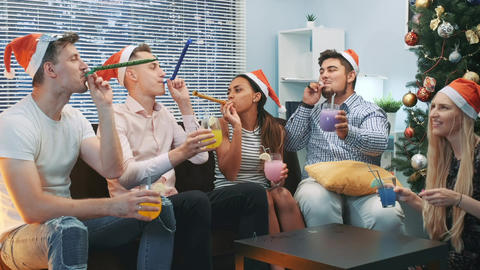 Best friends making cheers and blowing party whistle on Christmas party Live Action