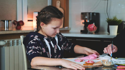 Cheerful young girl helping her mother to decorate cookies for the holiday Live Action