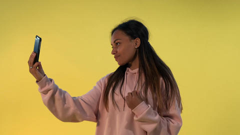 Cheerful mixed-race lady making selfie on smartphone on yellow background Live Action