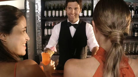 Waiter serving cocktail to customers Live Action