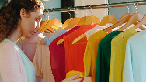 Woman choosing clothes from clothes rack Live Action