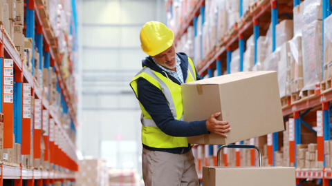 Warehouse worker suffering from back pain while working Live Action