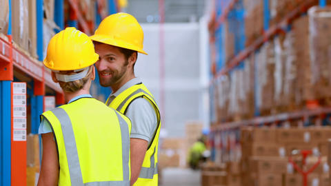 Male and female warehouse worker inspecting stock Live Action