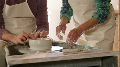 Mid-section of male potter assisting female potter Footage
