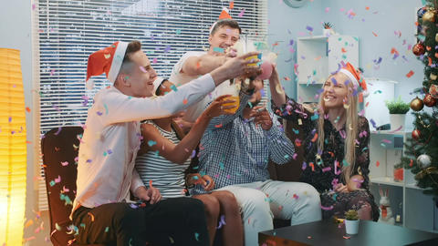 Close up of cheerful company celebrating Christmas in confetti blowing Live Action
