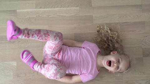 Emotion active girl child lying on floor move and shout. Gimbal motion shot Live Action