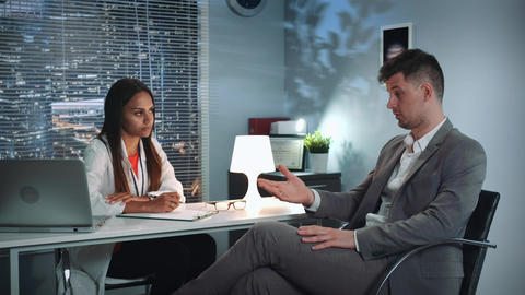 Psychologist therapy session: businessman sharing his problems with specialist Live Action