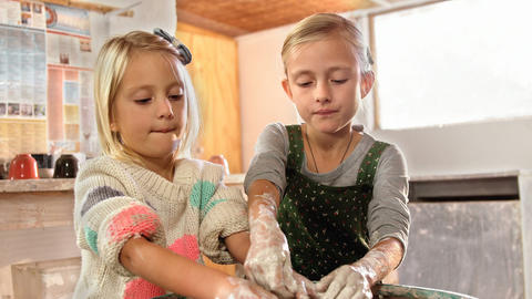 Girl assisting her sister while making a pot Footage