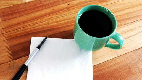 Close-up of coffee mug with blank paper and pen, Live Action