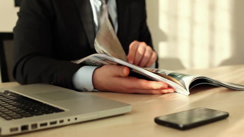 Young businessman reading magazine by desk at office Live Action