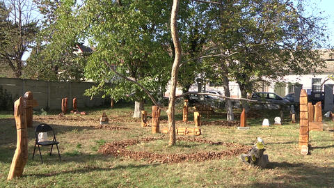 Wooden carving camp in a garden with leafy trees with randomly placed carved wooden objects bordered Live Action