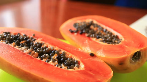 Exotic tropical fruit on table. Thai fruit. Papaya fruit cut in half. close-up Live Action