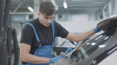 Cheerful young service man dancing as cleaning windshield of vehicle in repair Live Action