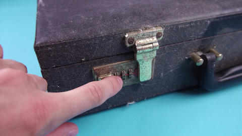 person presses button to open old dirty case on light blue Live Action