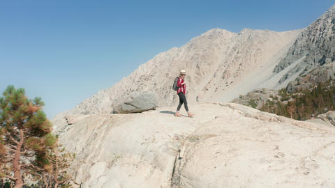 Woman enjoying mountains, spreading hands into air happy about freedom feeling Live Action