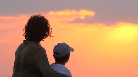 Silhouette of mother and child. Woman and child looking on sunset. Mother and Live Action
