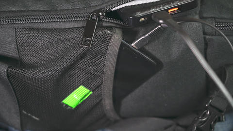 Smartphone charging. the mobile phone is charged from a power bank lying on a backpack Live Action