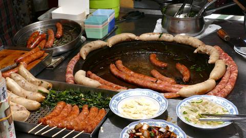 Cooking sausages in large frying pan on night market in Tainan ライブ動画