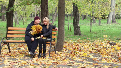 An adult couple sits on a bench in a forest park, talks and laughs, a man and a Live Action