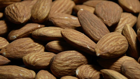A scattering of dried almonds on a dark background, a pile of nuts, camera movement Live Action