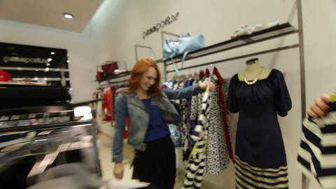 Cheerful women look at elegant striped dresses in store Live Action