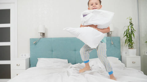 SLow motion of cheerful toddler boy holding pillow and jumping up high on bed at Live Action