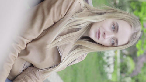 Vertical video of a young skinny girl in the park. Girl talking with someone Live Action