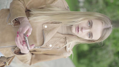 Vertical video of a young skinny girl in the park. Girl with a mobile phone Live Action