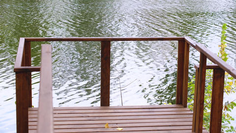 Part of wooden railings of empty bridge on a flowing river background Live Action