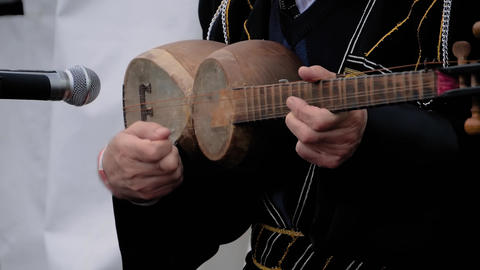 Slow motion: man hands playing azerbaijani tar on stage of open air concert Live Action